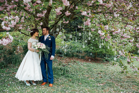 Bride and groom standing under a cherry tree in full blossom at their springtime wedding reception at Busbridge Lakes