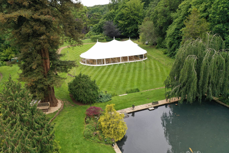 Celeste pole tent marquee on the Canal Lake's venue at Busbridge Lakes for a wedding reception seen from the air