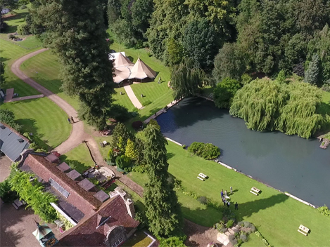 Tipis on the Canal Lake venue at Busbridge Lakes for a wedding reception seen from the air