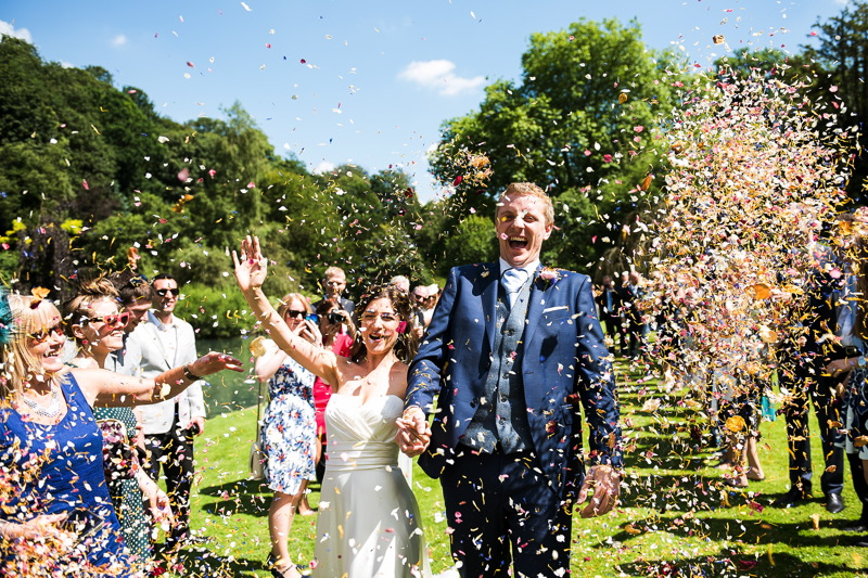 Bride and groom smiling as they walk though their confetti line on the ceremony lawn beside Busbridge Lakes' Canal lake