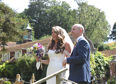 Just married bride and groom at the top of the steps leading to their wedding breakfast with Busbridge Lakes' coach house in the background