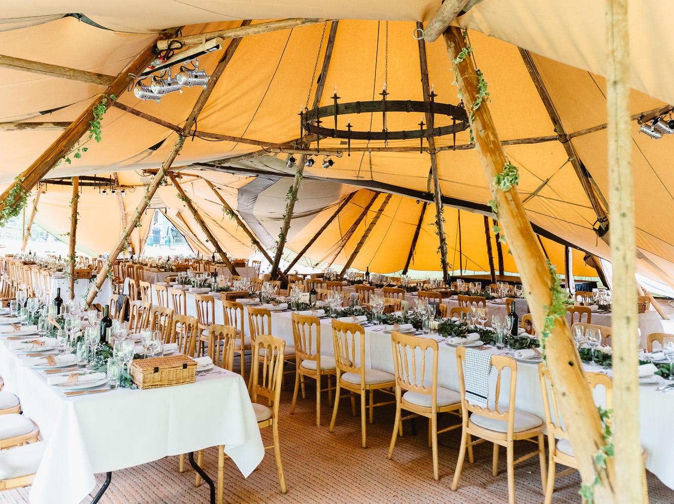 Juniper runners on long tables with white tablecloths inside a tipi