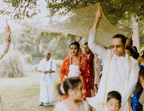 Hindu bride possession with South Indian and Mauritian priests on the way to her countryside wedding ceremony under the Cedar tree at Busbridge Lakes