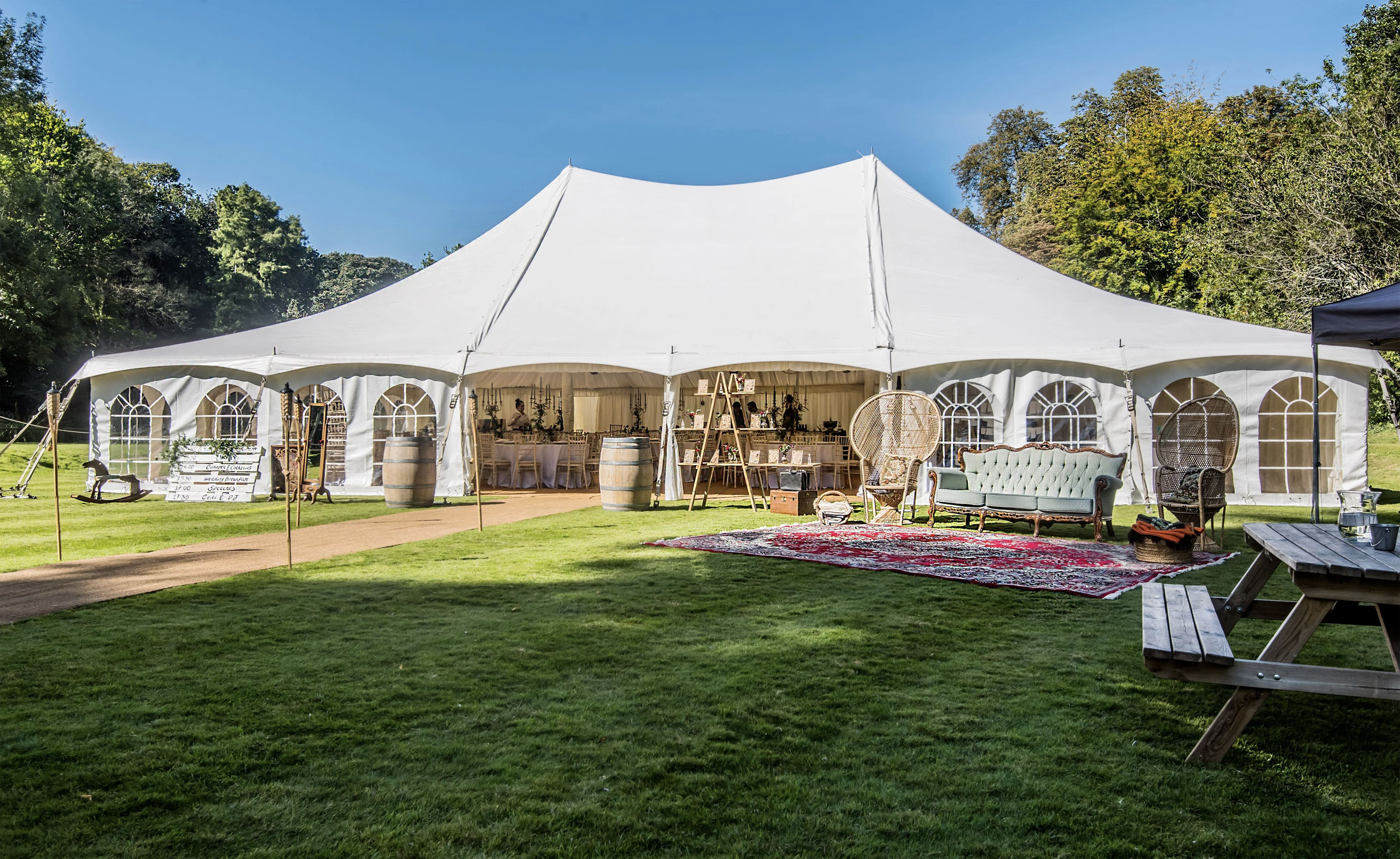 60 x 40 foot metal pole tent marquee on the Canal Lake venue for a garden wedding reception with relaxing furniture and props outside