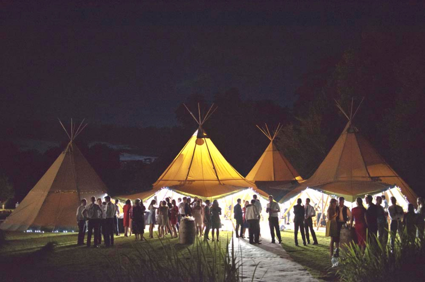 3 tipi hats illuminated at night on the Canal Lake venue at Busbridge Lakes for a lakeside wedding reception