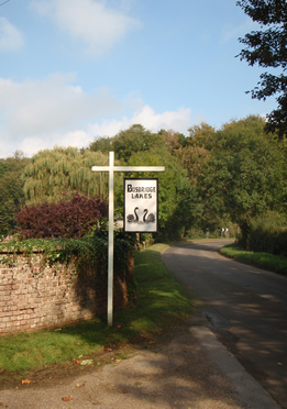 Road sign with 2 black swans on marking the entrance to Busbridge Lakes